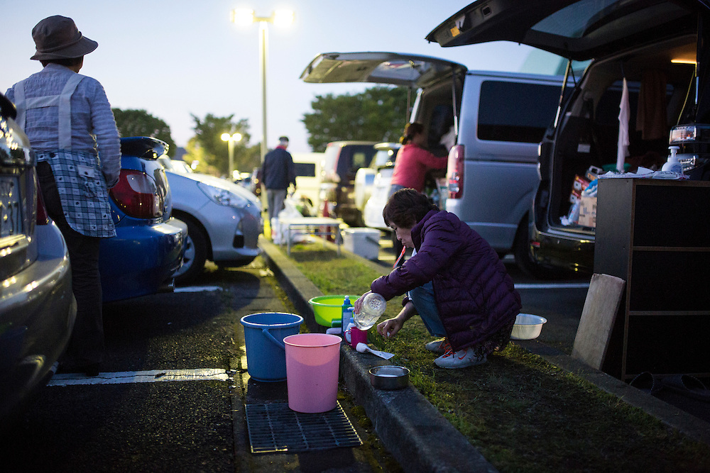 KUMAMOTO, JAPAN - APRIL 19: Residents wash their plates after eating in the carpark of Mashiki Gymnasium evacuation center on April 19, 2016 in Mashiki, Kumamoto, Japan. quake Survivors face health threat, health experts says, 20 people diagnosed in Mashiki, one has died and 2 are in critical condition NHK reports.<br /> <br /> Photo: Richard Atrero de Guzman