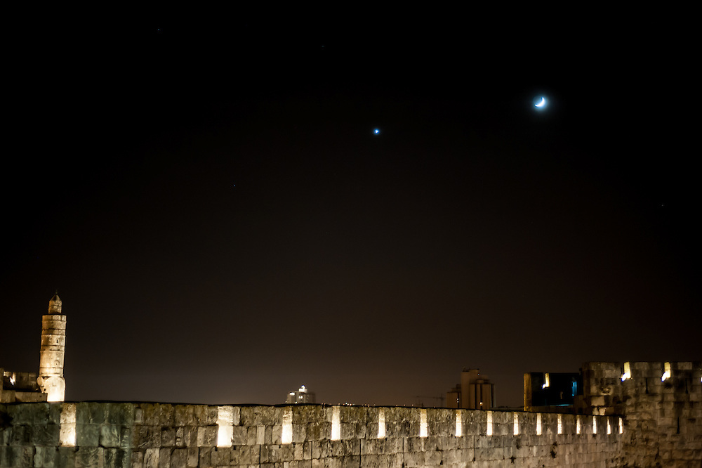 Venus and the sliver of a waxing moon rise over the city walls of Jerusalem