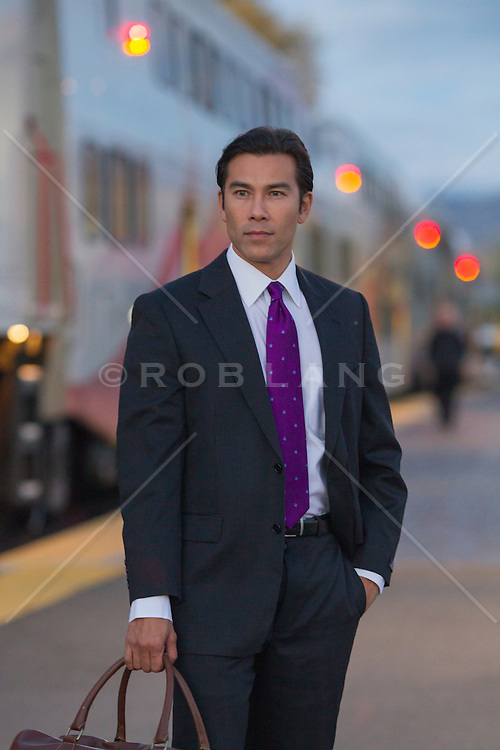 Asian American businessman standing by a train at dusk in Santa Fe, NM