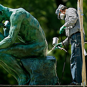 "Bob Marti, an art conservator with Russell-Marti Conservation Services of California, Mo., applied a coat of acrylic laquer by sprayer to a bronze sculpture of ""The Thinker,"" by Auguste Rodin, in the Kansas City Sculpture Park on the south steps of the Nelson-Atkins Museum of Art in Kansas City, Mo. on September 13, 2006."