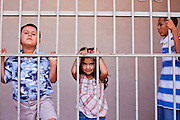 """10 OCTOBER 2010 - PHOENIX, AZ:  Children watch Matachine dancers from behind a fence in Phoenix. About 500 people processed through downtown Phoenix Sunday afternoon to honor the Virgin of Guadalupe, the """"Queen of the Americas."""" The procession was accompanied by 12 Matachine dance troupes. The Matachines are an important part of Mexican Catholic culture. They represent the battle of Good vs. Evil and the protect the Virgin from malevolent forces, represented by the demon like figures who accompany the dancers.      Photo by Jack Kurtz"""