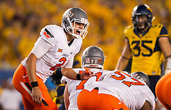 Oct 10, 2015; Morgantown, WV, USA; Oklahoma State Cowboys quarterback Mason Rudolph changes the play at the line of scrimmage during the first quarter against the West Virginia Mountaineers at Milan Puskar Stadium. Mandatory Credit: Ben Queen-USA TODAY Sports