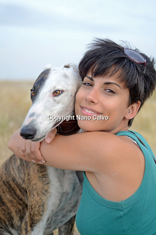 Young attractive woman with her Spanish greyhound in nature