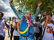 23 JUNE 2016 - MAHACHAI, SAMUT SAKHON, THAILAND:   A man in traditional Burmese clothing dances while waiting for Aung San Suu Kyi to arrive in Samut Sakhon, a province south of Bangkok. Tens of thousands of Burmese migrant workers, most employed in the Thai fishing industry, live in Samut Sakhon. Aung San Suu Kyi, the Foreign Minister and State Counsellor for the government of Myanmar (a role similar to that of Prime Minister or a head of government), is on a state visit to Thailand. Even though she and her party won the 2015 elections by a landslide, she is constitutionally prohibited from becoming the President due to a clause in the constitution as her late husband and children are foreign citizens      PHOTO BY JACK KURTZ