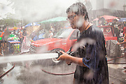 14 APRIL 2013 - BANGKOK, THAILAND:  A man uses a fire hose on people in a water fight on April 14, 2013 in Bangkok, Thailand. The Songkran festival is celebrated in Thailand as the traditional New Year's Day from 13 to 15 April. The throwing of water originated as a way to pay respect to people and is meant as a symbol of washing all of the bad away. PHOTO BY JACK KURTZ
