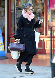(EXCLUSIVE PICTURES) Actress Helena Bonham Carter wearing a grey beanie hat, pink fur scarf, blue coat, woolly socks, and wedge shoes out Christmas shopping in north London, UK. 02/12/2019<br />