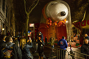 New York, NY – 27 November 2019. Thousands of spectators packed the streets around the American Museum of Natural History to see the inflation area for the balloons for Macy's Thanksgiving Day Parade. A family  pauses for photos, with Astronaut Snoopy in the background.,