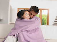 Young Affectionate Couple Wrapped in Blanket