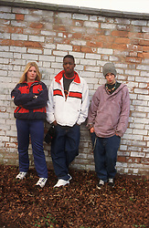 Multiracial group of youths standing against brick wall looking serious,