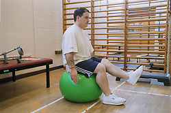 Rehabilitation session in gym with patient doing balance work with therapy ball,