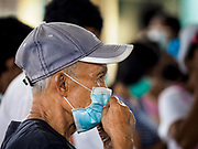 24 JANUARY 2018 - GUINOBATAN, ALBAY, PHILIPPINES: A man adjusts his breathing filter during a volcanic ash fall in Guinobatan. The Mayon volcano continued to erupt Tuesday night and Wednesday forcing the Albay provincial government to order more evacuations. By Wednesday evening (Philippine time) more than 60,000 people had been evacuated from communities around the volcano to shelters outside of the 8 kilometer danger zone. Additionally, ash falls continued to disrupt life beyond the danger zones. Several airports in the region, including the airport in Legazpi, the busiest airport in the region, are closed indefinitely because of the amount of ash the volcano has thrown into the air.    PHOTO BY JACK KURTZ