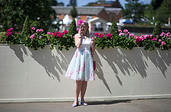 © Licensed to London News Pictures. 21/06/2018. London, UK. A Racegoer with hair matching the flowers she is standing next to, taks on the phone at Ladies Day at Royal Ascot at Ascot racecourse in Berkshire, on June 21, 2018. The 5 day showcase event, which is one of the highlights of the racing calendar, has been held at the famous Berkshire course since 1711 and tradition is a hallmark of the meeting. Top hats and tails remain compulsory in parts of the course. Photo credit: Ben Cawthra/LNP