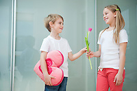Little boy with heart shape cushion giving flower to girl