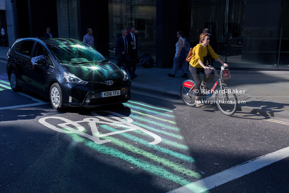In an area of reflected light, a cyclist pedals along Threadneedle Street alongside a car in the City of London - the capital's financial centre (aka The Square Mile), on 27th September 2018, in London, England.