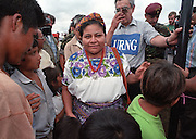 1992 Nobel peace prize winner Rigoberta Menchu Tum, a Mayan Indian woman from war-torn Guatemala, holds a child during a visit to a rural village as part of the peace process.