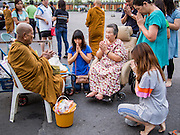 """14 FEBRUARY 2014 - BANGKOK, THAILAND:  Thai Buddhists make merit on Makha Bucha Day at Wat That Thong (also called Wat Tad Tong) in Bangkok. The aims of Makha Bucha Day are: not to commit any kind of sins, do only good and purify one's mind. It is a public holiday in Cambodia, Laos, Myanmar and Thailand. Many people go to the temple to perform merit-making activities on Makha Bucha Day. The day marks four important events in Buddhism, which happened nine months after the Enlightenment of the Buddha in northern India; 1,250 disciples came to see the Buddha that evening without being summoned, all of them were Arhantas, Enlightened Ones, and all were ordained by the Buddha himself. The Buddha gave those Arhantas the principles of Buddhism, called """"The ovadhapatimokha"""". Those principles are:  1) To cease from all evil, 2) To do what is good, 3) To cleanse one's mind. The Buddha delivered an important sermon on that day which laid down the principles of the Buddhist teachings. In Thailand, this teaching has been dubbed the """"Heart of Buddhism.""""   PHOTO BY JACK KURTZ"""