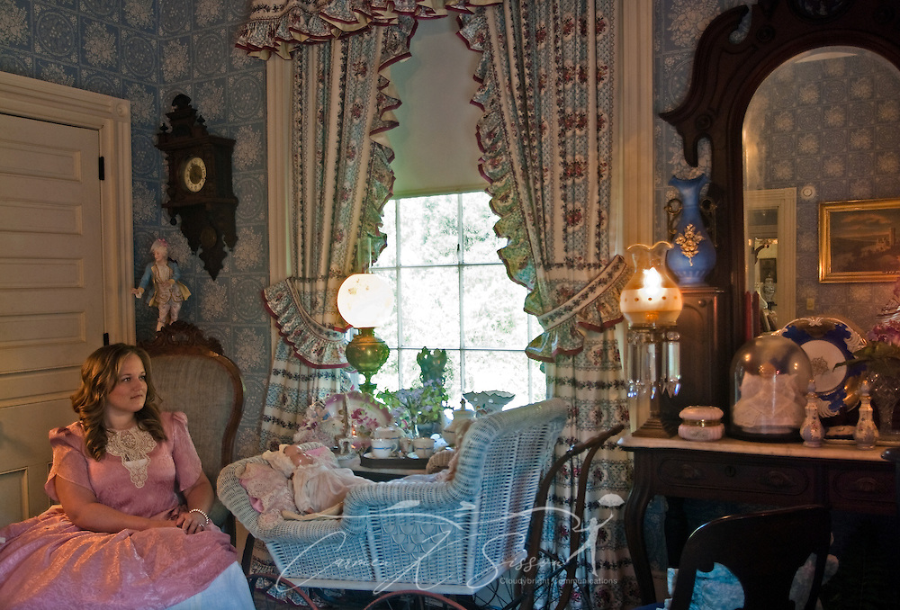 """Cindy Bryant sits beside a vintage baby crib in the """"Blue Room"""" at Rosewood Manor in Columbus, Miss. April 16, 2010. The 1835 Greek-Revival antebellum mansion was among nearly two dozen on tour during Columbus' annual Spring Pilgrimage. (Photo by Carmen K. Sisson/Cloudybright)"""