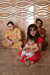 © Licensed to London News Pictures. Hamdaniyah, Iraq. 25/07/2014. Hamdaniyah, Iraq.  Dilar Minowar Salim (9), a female Iraqi Christian refugee holds a young relative inside the kitchen of the unfinished house they share with their extended family in Hamdaniyah, Iraq. She left Mosul on Friday the 18th of July when Islamic State fighters issued an ultimatum to the city's Christian community. When the family left they were forced to pay a tax for their car, and one member was threatened at knifepoint to ensure they handed over all of their possessions.<br /> <br /> <br /> Having taken over Mosul Iraq's second largest city in June 2014, fighter of the Islamic State (formerly known as ISIS) have systematically expelled the cities Christian population. Despite having been present in the city for more than 1600 years, Christians in the city were given just days to either convert to Islam, pay a tax for being Christian or leave; many of those that left were also robbed at gunpoint as they passed through Islamic State checkpoints.. Photo credit : Matt Cetti-Roberts/LNP