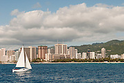 A sailboat heads into Waikiki Beach.
