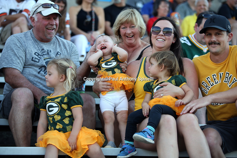 A group of Green Bay Packers fans look on while their daughters are dressed in team logo'd tutus, one of whom cries with a pained expression of sorrow on her face, much like the fans who didn't get to see the game, before the Green Bay Packers 2016 NFL Pro Football Hall of Fame preseason football game against the Indianapolis Colts on Sunday, Aug. 7, 2016 in Canton, Ohio. The game was canceled for player safety reasons due to the condition of the paint on the turf field. (©Paul Anthony Spinelli)
