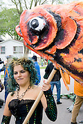 Puppeteer age 22 holding fish which represents beings who live in water. MayDay Parade and Festival. Minneapolis Minnesota USA