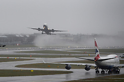 A plane takes over despite heavy rain and strong winds at Heathrow's Terminal 5.<br /> Christmas travellers leave for their festive holidays at Heathrow Airport. Monday, 23rd December 2013. Picture by Ben Stevens / i-Images