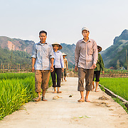 CAPTION: Chung walks to his rice field with neighbouring farmers, who he recently trained on sustainable rice cultivation. Rather than working directly with individuals, We Effect acts in partnership with four community-based organisations (CBOs): the Women's Association, the Farmers' Association, the Veterans' Association and the Youth Union. After strengthening the CBOs' capacities through leadership training, 25 members from each are selected to receive training to themselves become trainers on innovative and environmentally-friendly cultivation and livestock breeding techniques. Once trained, each individual then transfers his or her technical knowledge to at least two other members of his or her CBO. This is a cost-effective way of sharing knowledge that also serves to strengthen each organisation. LOCATION: Coong Village, Huy Tuong, Son La Province, Vietnam. INDIVIDUAL(S) PHOTOGRAPHED: From left to right: Cam Tuan Nuon, Ha Thi Sien and Vi Van Chung.