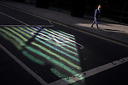 Pedestrian walks past reflected green light from nearby office building plate glass.