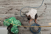 A deck hand from the schooner Appledore II coils a hose on the dock in Camden, Maine.