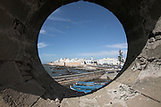 Circular hole in rampart walls giving view of the coast and town medina, Essaouira, Morocco