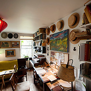 May 10, 2012 - Brooklyn, NY : The living room in musician and composer Michael Arenella's apartment on Douglas Street in Brooklyn is adorned with a collection of hats, musical instruments, and paintings by his father, Joe Arenella (the single paiting at right) and by his great uncle Walter Senyk (the three paintings at left). CREDIT : Karsten Moran for The New York Times