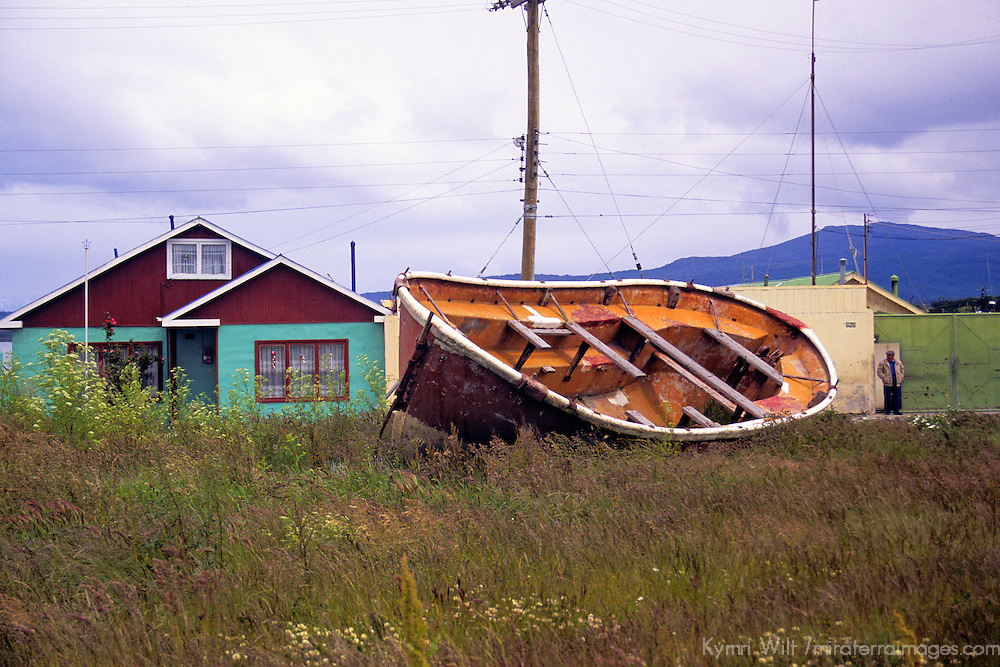 Americas, South America, Chile, Puerto Natales. A house, a boat, and a man in Puerto Natales.