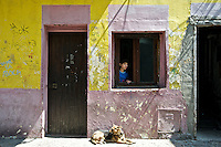 A boy looks out the window in the colorful barrio of La Boca in Buenos Aires, Argentina
