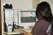 Young female Graphic artist working with Photoshop on her PC work station seen from the back