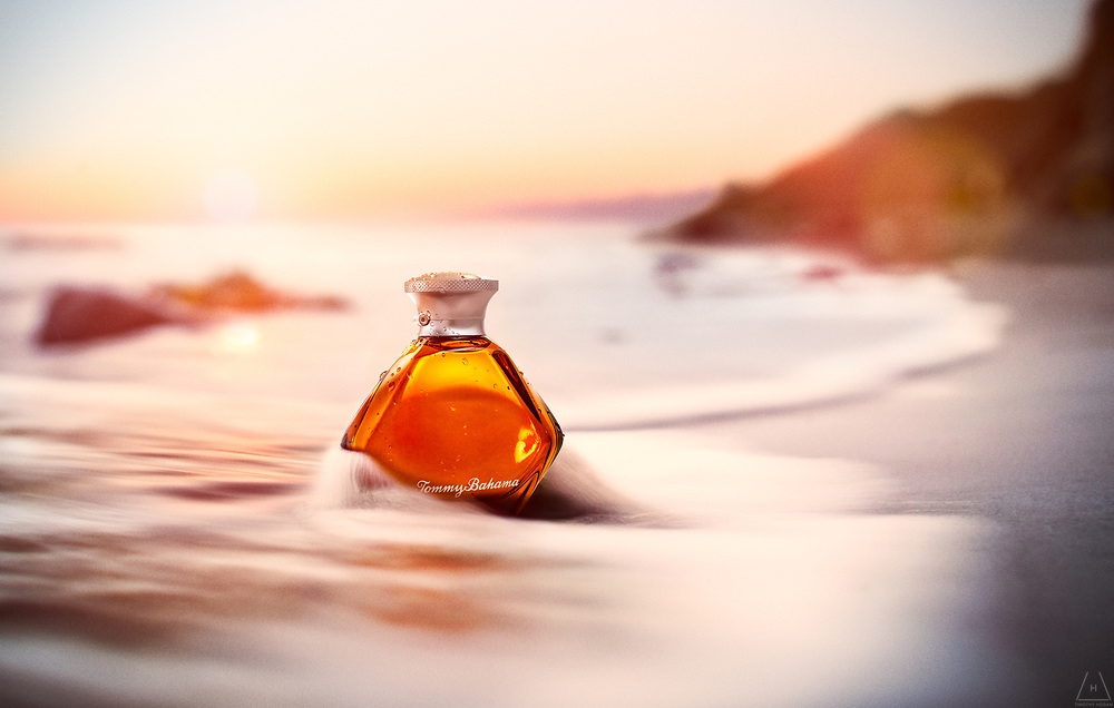 Tommy Bahama Cognac For Men spray bottle set on the beach amidst a crashing wave with the backdrop of a setting sun