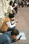 young adults text messaging Japan Tokyo outside Shibuya station