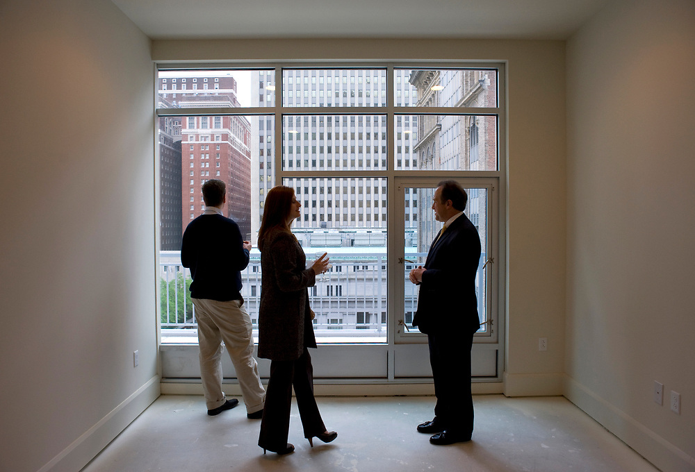 Director of Sales Mark Jennings (right) gives Andreas Beck (left) and his wife Melanie Querry a tour of the penthouse apartment during a Pittsburgh Ballet Theater party at Piatt Place in Pittsburgh.  Querry is the president and founder of Beyond Spots and Dots advertising agency.