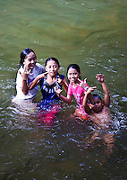 Iban children from Nanga Sumpa Longhouse enjoy an afternoon playing and swimming in the river, Sarawak.