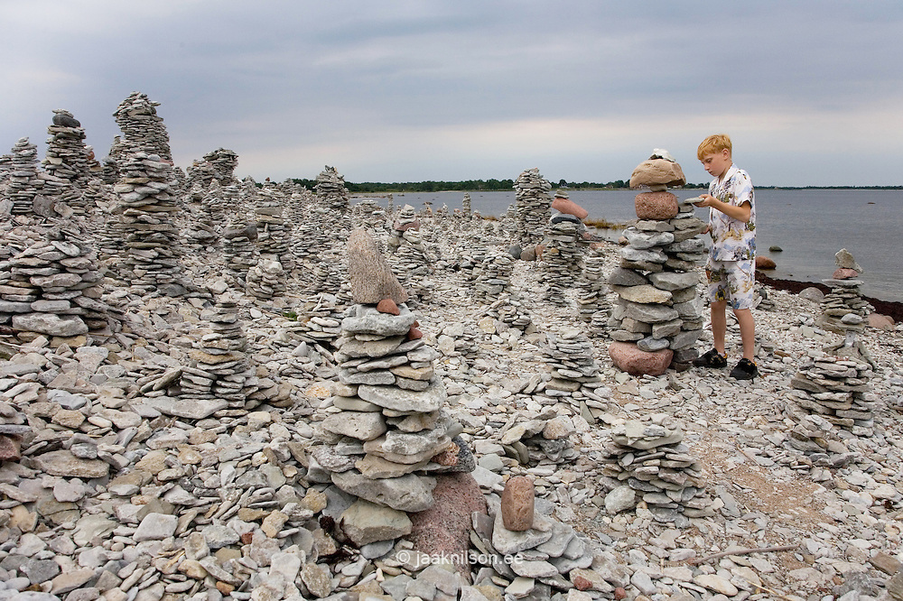 Boy Building Stone Tower by Baltic Sea Coast, Saaremaa, Saare County, Estonia. Stones piled up as tower at beach.