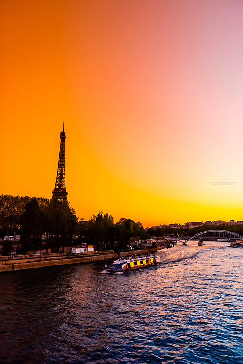 A Bateau mouche  (ship) on the River Seine passes in front of the Eiffel Tower at sunset, Paris, France.