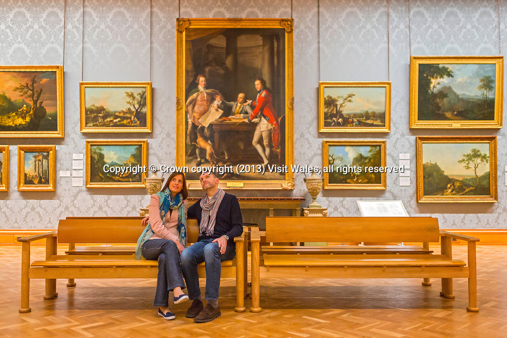 Couple sitting in Historic Gallery looking up at paintings<br /> National Museum<br /> Cardiff<br /> South<br /> Museums<br /> Tourist Attractions