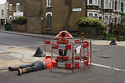 At a road junction, contractors drag cables along underground channels in Railton Road, Brixton.