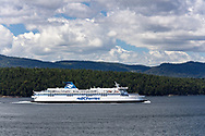 The BC Ferries ship Spirit of Vancouver Island (built in 1994) in Trincomali Channel on the way to Tsawwassen from Victoria (Swartz Bay).  Photographed from Village Bay at Mayne Island, British Columbia, Canada.  Mountain peaks in the clouds (background, left) appears to be in the Olympic Range.