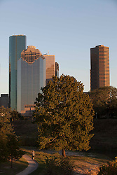 Man enjoying the Hike & Bike Trail in Buffalo Bayou Park with the downtown Houston skyline in the background.