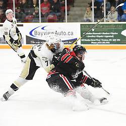 TRENTON, ON - Apr 18, 2016 -  Ontario Junior Hockey League game action between the against the Trenton Golden Hawks and the Georgetown Raiders. Game 3 of the Buckland Cup Championship Series, at the Duncan Memorial Gardens in Trenton, Ontario. Brandon Marinelli #7 of the Trenton Golden Hawks makes the hit on Daniel Hardie #15 of the Georgetown Raiders during the third period.<br /> (Photo by Andy Corneau / OJHL Images)