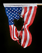 American flag with an hole burned in it against a black background