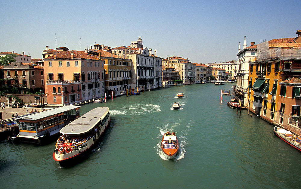 Venice, Italy: High Noon on the Grand Canal, as seen from the Ponte dell'Accademia.  One of the city's busiest vaporetto stations is on the left; a launch, possibly carrying tourists from the airport to their hotel is in the center.