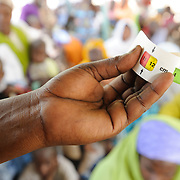 A community health worker displays a Mid Upper-Arm Circumference (MUAC) tape, used to in screening children for malnutrition at a Save the Children therapeutic feeding centre in the village of Koona in the Tessaoua region of Niger.