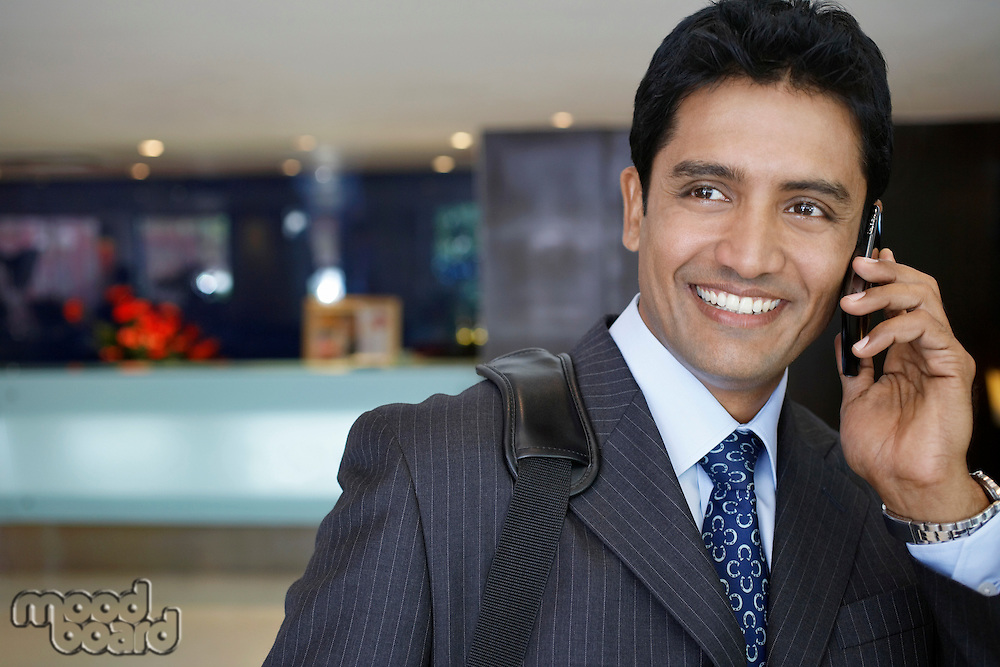 Business man using mobile phone in hotel lobby