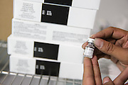 Cold store assistant manager Eddy Godoy holds a vaccine vial inside a refrigerated storage area at the PAI (Programa Ampliado de Inmunizaciones) offices in Tegucigalpa, Honduras, on Wednesday April 24, 2013..